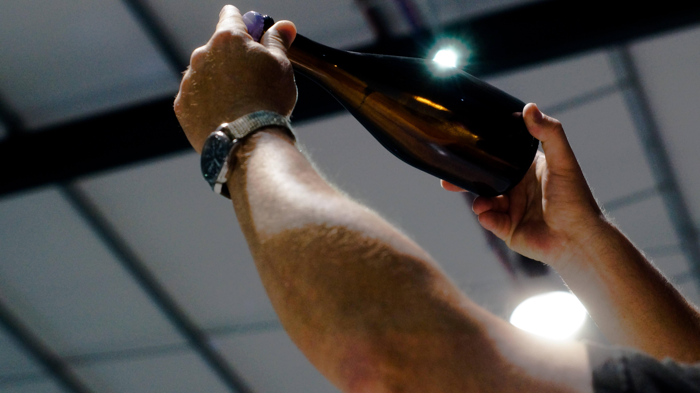 Mark holding a plain Rathfinny Reserved bottle up to the light