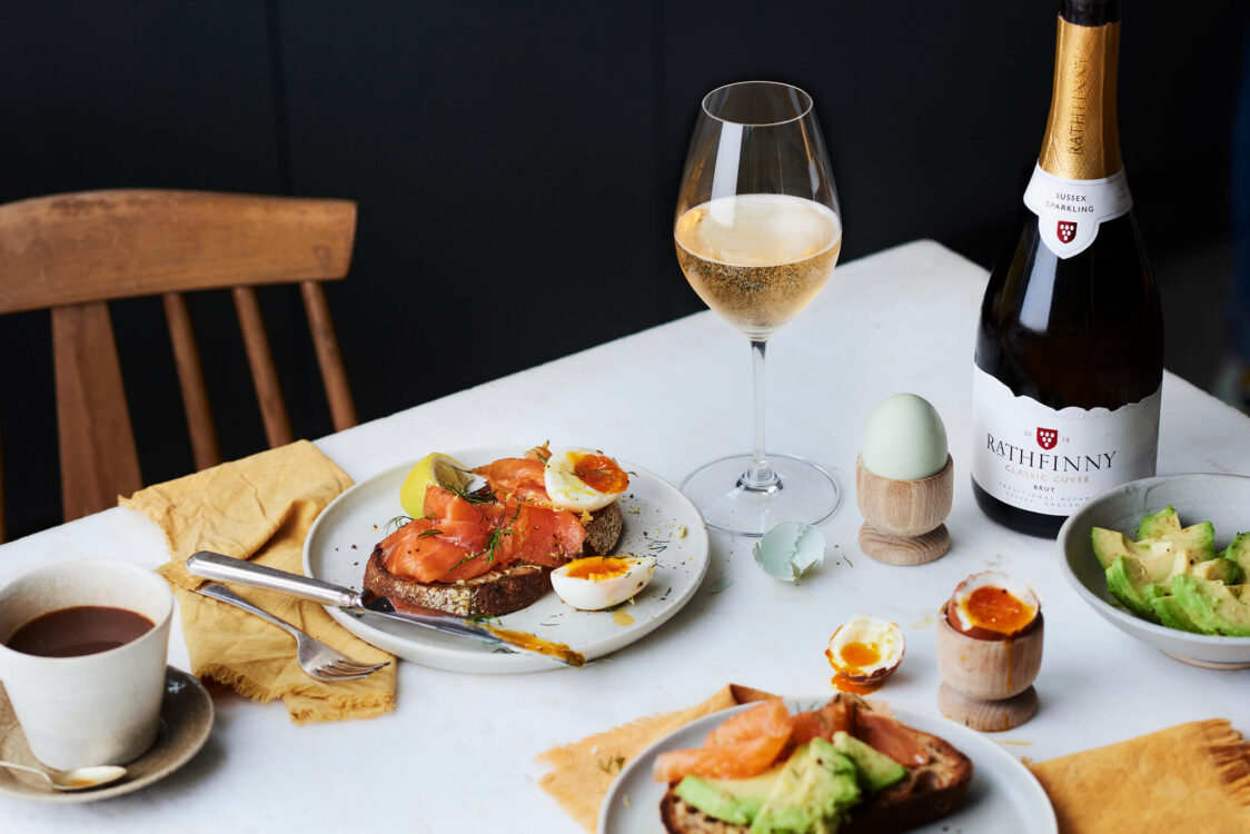 A table set for brunch with a glass of Sussex Sparkling wine, toast, salmon, eggs and avocado